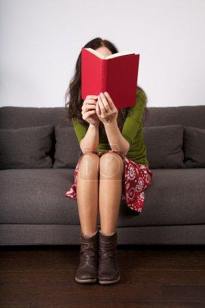 Photo pour Détail femme assise sur un canapé marron lisant un livre - image libre de droit