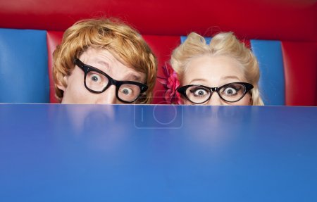 Nerdy couple hiding behind a table