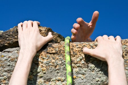 Hands of climber on brink of rock needing the help...