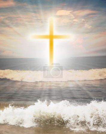Foto de Símbolo religioso cristiano cruz contra el sol brillan en el fondo y las olas del océano en primer plano - Imagen libre de derechos