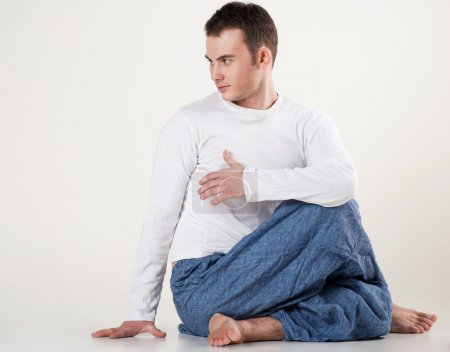 Healthy young man doing yoga. Spine twisting pose