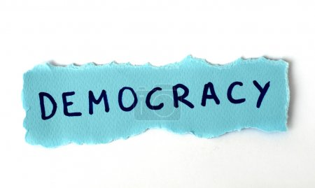 The word Democracy on blue paper