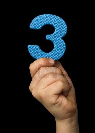 Photo pour Les enfants tiennent le numéro 3. Noir isolé numéro bleu Trois - image libre de droit