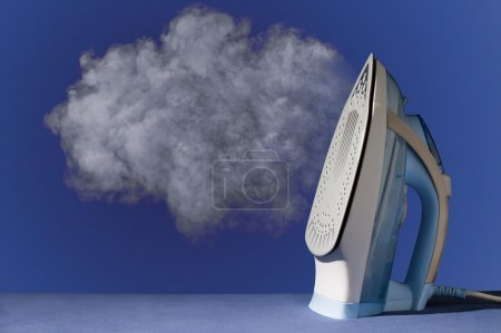 Photo for Hot vertical new iron throws cloud of white steam on blue background - Royalty Free Image