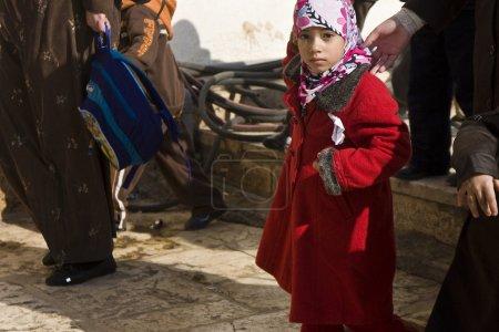 Photo pour Une jeune fille musulmane, je regarde le photographe sur sa route vers fermé l'école sur le Mont temple, Jérusalem. étrangers ne sont pas autorisés dans la région à l'exception de plusieurs ho - image libre de droit