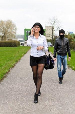 Photo pour Voleur suit sa victime à l'aube dans la rue - image libre de droit