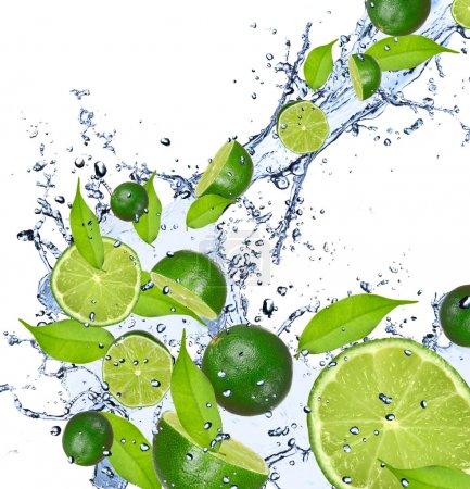 Photo pour Limes tombant dans les éclaboussures d'eau, isolés sur fond blanc - image libre de droit