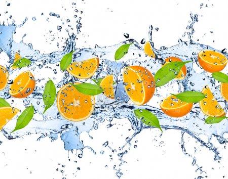 Photo pour Morceaux frais d'oranges tombant dans l'éclaboussement de l'eau, isolé sur fond blanc - image libre de droit