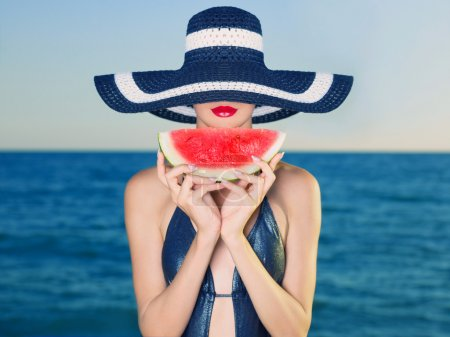 Photo pour Young stylish lady in a hat at sea with watermelon - image libre de droit