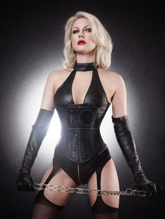 A young blond lady mistress with bright red lips without any emotions standing in a pose, wearing a black leather corset and gloves on the black background with the white flash light behind the model