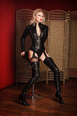 A young blond sexy lady mistress with bright red lips wearing a black leather costume