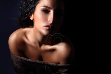 Young Italian fashion model portrait with perfect skin on dark blue background