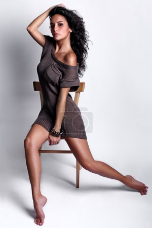 Sexy Italian dancer model posing sitting on a chair in a studio white background wearing brown knitted dress