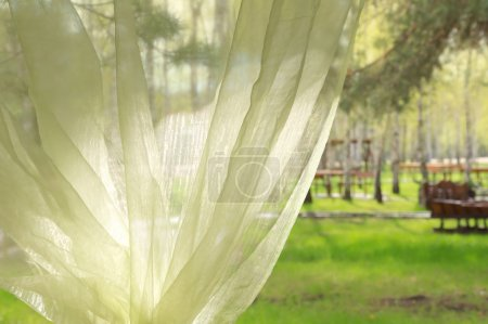 Photo for Window with green curtains and spring park behind it - Royalty Free Image