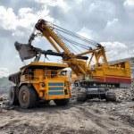Loading of iron ore on very big dump-body truck HD...