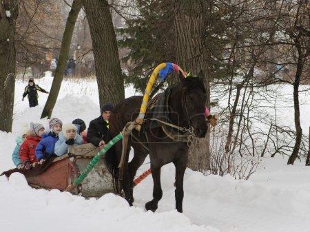 Photo pour Les enfants monter à cheval dans le parc sur le mardi gras en hiver - image libre de droit