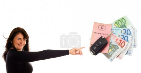 Woman pointing to a car key and notes