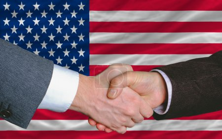 Photo for Two businessmen shaking hands after good business investment agreement in america, in front of flag - Royalty Free Image