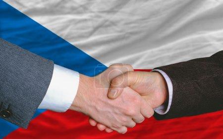 Businessmen handshake after good deal in front of czech flag