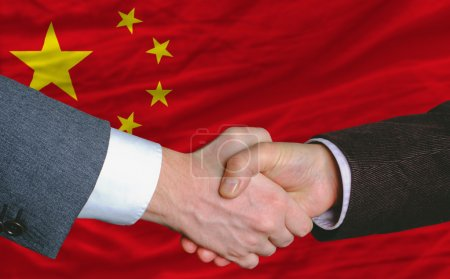 Businessmen handshakeafter good deal in front of china flag