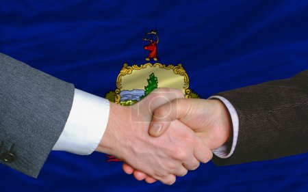 In front of american state flag of vermont two businessmen hands
