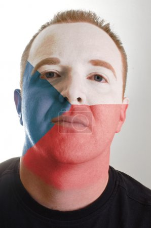 Face of serious patriot man painted in colors of czech flag