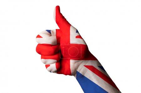 Photo pour Main avec le pouce vers le haut de geste coloré dans le drapeau national de la Grande-Bretagne comme symbole d'excellence, réussite, bonne, - utile pour le tourisme et publicité touristique et aussi actuelle gestion positive de sociale, culturelle et politique de l'État ou du pays - image libre de droit