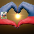 Постер, плакат: Heart and love gesture by hands colored in haiti flag during bea