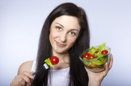 Photo for Portrait of pretty young girl eating vegetable salad - Royalty Free Image