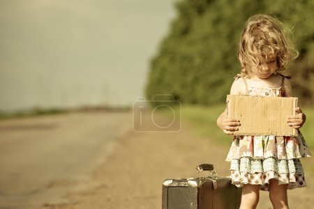 Photo for Lonely girl with suitcase standing about road and holding paper with copyspace in hands - Royalty Free Image
