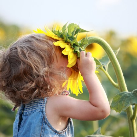 Photo for Cute child with sunflower in summer field - Royalty Free Image