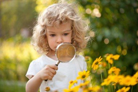 Photo pour Fleurs enfant explorateur mignon dans le jardin - image libre de droit