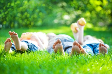 Photo for Children laying on grass. Family picnic in spring park - Royalty Free Image