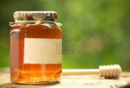 Photo pour Pot de miel avec étiquette en papier vierge et bâton de bois sur la table sur fond vert printemps naturel - image libre de droit