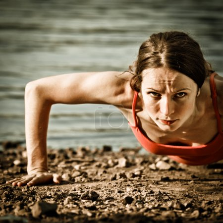 Photo for Strong woman doing pushups at the beach - Royalty Free Image