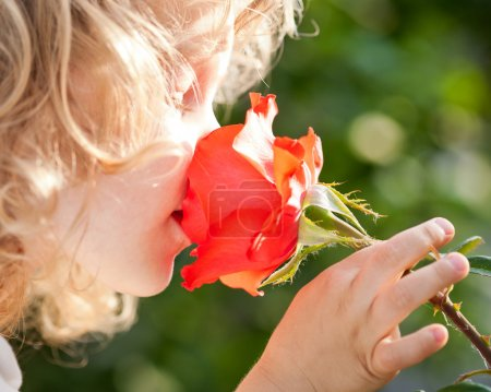 Photo for Beautiful child with flower against spring green background. Ecology concept - Royalty Free Image