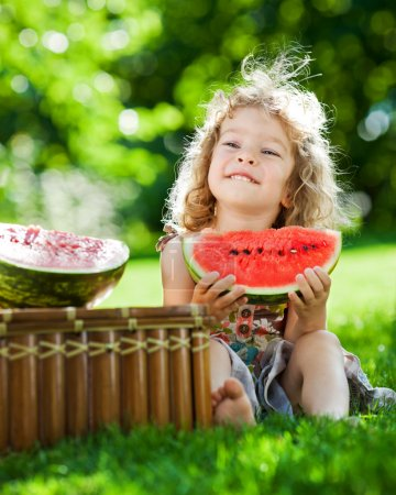 Photo for Happy smiling child eating watermelon outdoors in spring park - Royalty Free Image