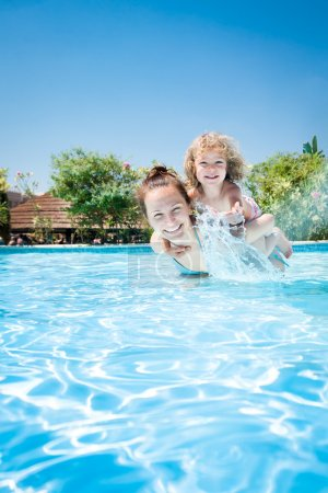 Foto de Happy kid playing with woman in swimming pool on a tropical resort at the sea. Summer vacations - Imagen libre de derechos