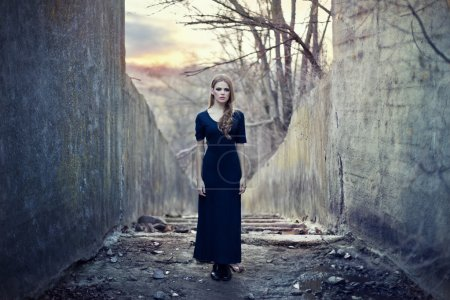 Photo for Beautiful lonely girl in long dress near gloomy tunnel on sunset - Royalty Free Image