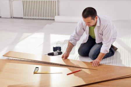 Foto de Mejoras para el hogar - hombre tendido nuevo laminado en habitación vacía - Imagen libre de derechos