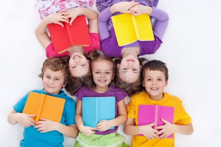 Photo for Happy kids laying on the floor holding books - the colorful world of reading - Royalty Free Image