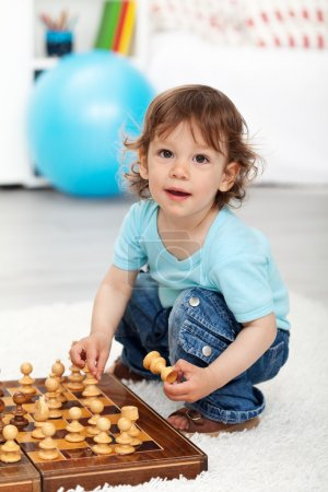 Photo for Adorable little boy playing with chess pieces indoors - Royalty Free Image