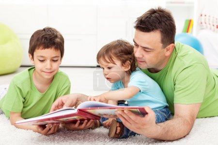 Photo pour Des enfants lisant un livre d'histoire avec leur père assis par terre - image libre de droit