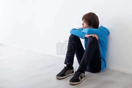 Photo for Serious teenager boy thinking and daydreaming while sitting at home - Royalty Free Image