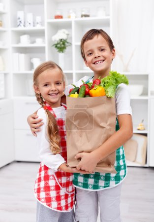 Photo for Happy healthy kids in the kitchen with the grocery bag full of vegetables - Royalty Free Image