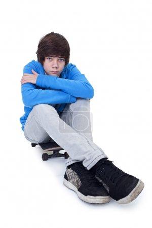Photo pour Adolescent assis sur son skateboard - isolé avec un peu d'ombre - image libre de droit