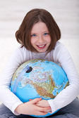 Young girl hugging earth globe