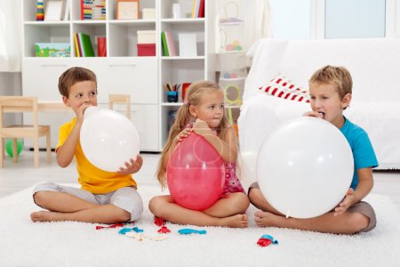 Kids blowing up balloons