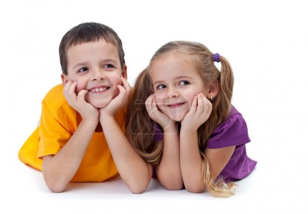 Photo for Smiling siblings laying down looking to the side - on white - Royalty Free Image