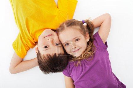 Photo pour Enfants heureux se détendre allongé sur blanc - vue sur le dessus - image libre de droit
